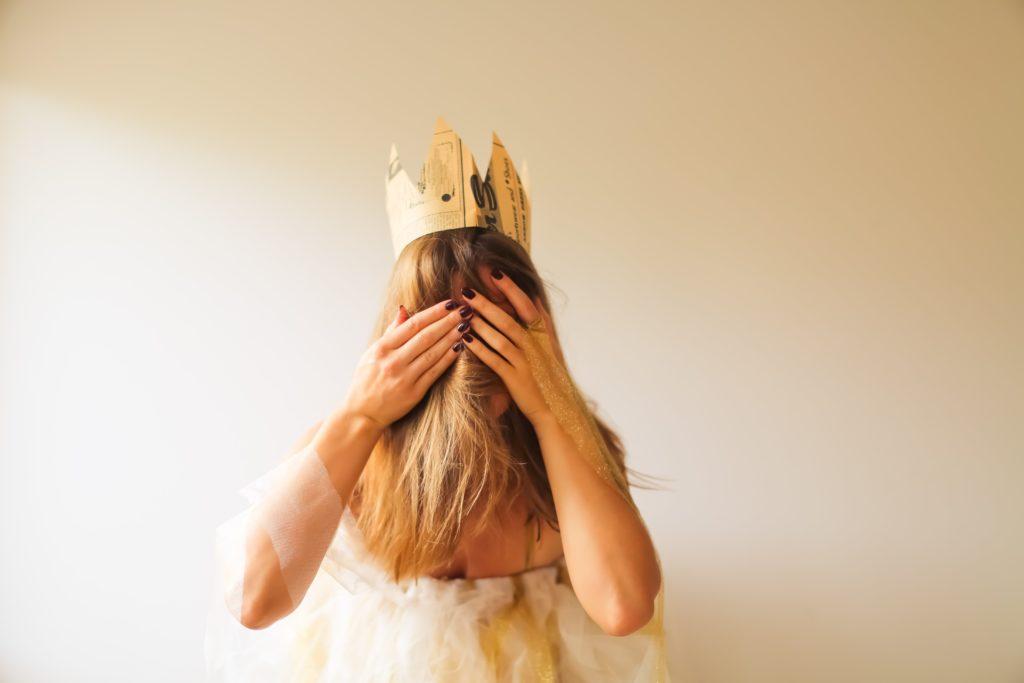 Foto de modelo fantasiada com uma coroa sobre a cabeça, como um personagem da realeza
