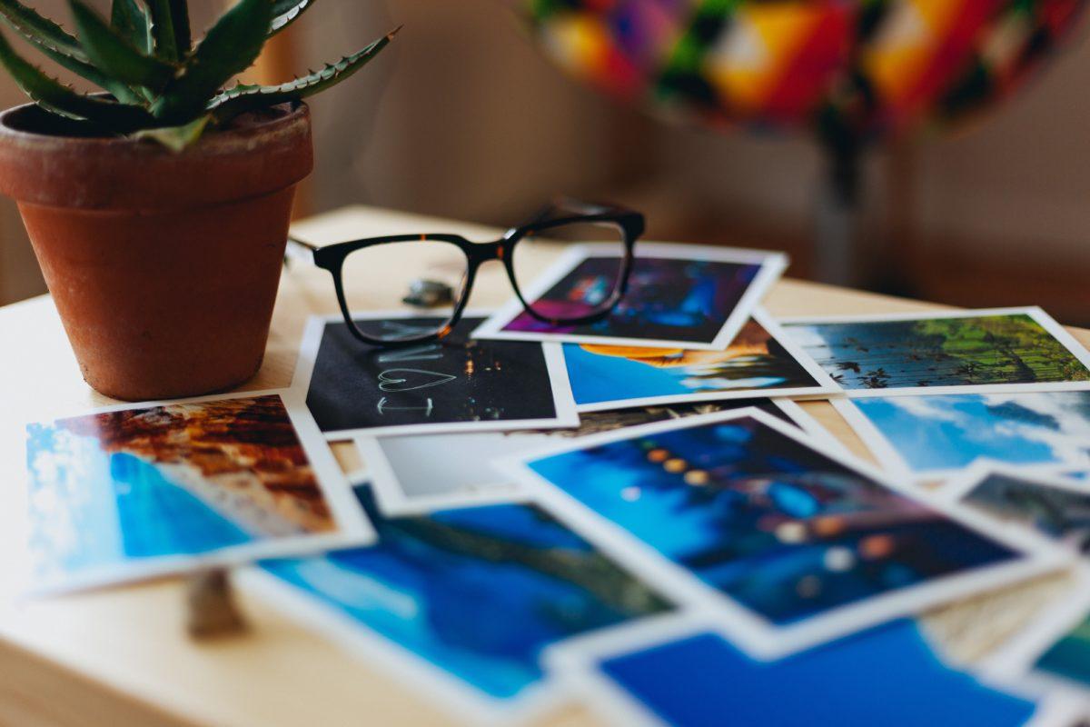 Foto: composição com diversas fotografias em papel fotográfico, dispostas sobre uma mesa.