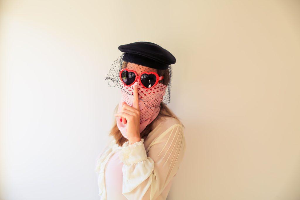 A mesma modelo da foto anterior agora se disfarça com óculos escuros e outros lenços e chapéus.