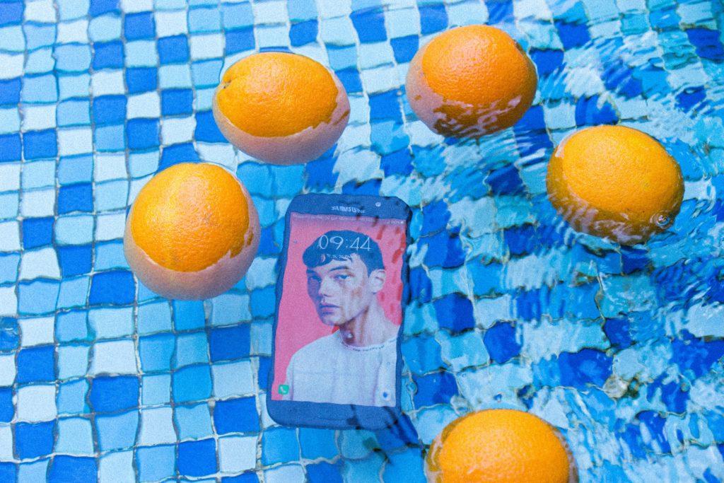foto em que um smartphone ligado está mergulhado em uma piscina, com algumas laranjas boiando ao seu redor