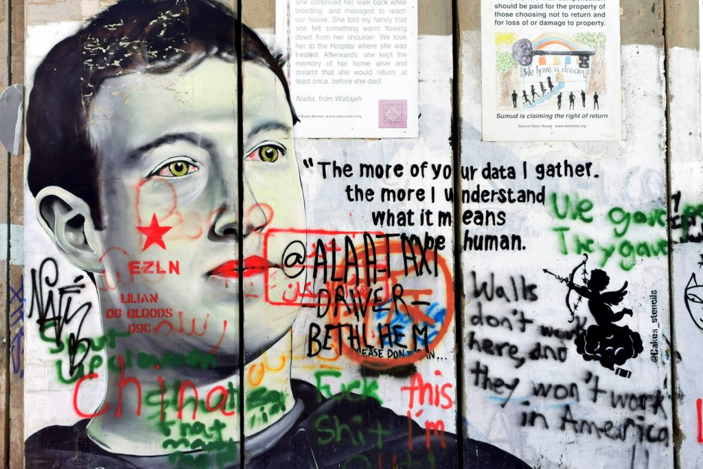 "grafite em muro onde podemos ver Mark Zuckerberg e uma frase supostamente atribuída a ele, que diz ""The more of your data I gather, the more I understand what it means to be human"" (Quanto mais eu coleto seus dados, mais eu entendo o que significa ser humano)"